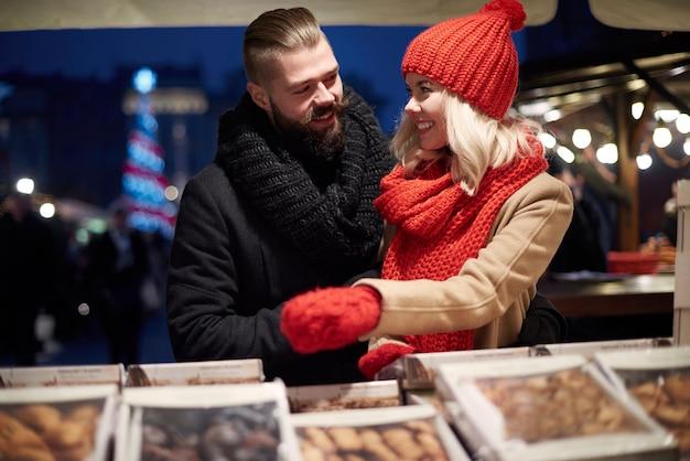 Casal apaixonado comprando doces no mercado local