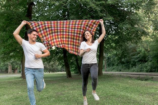 Casal apaixonado, correndo com um cobertor na natureza