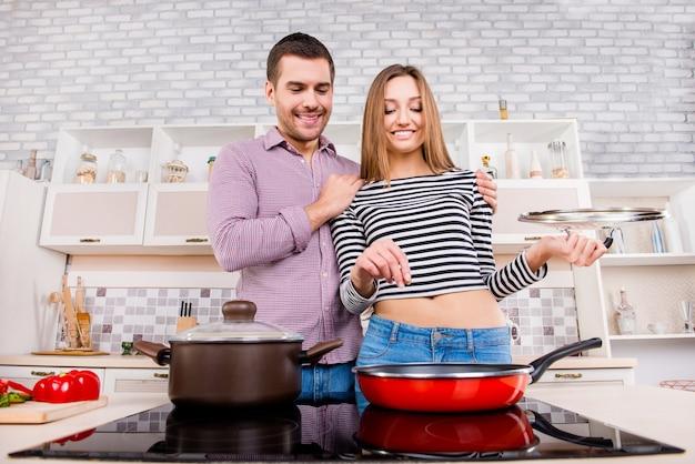 Casal apaixonado cozinhando na cozinha e omelete de sal