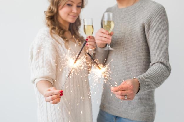 Casal apaixonado de ano novo segurando estrelinhas e taças de champanhe em close-up de parede branca