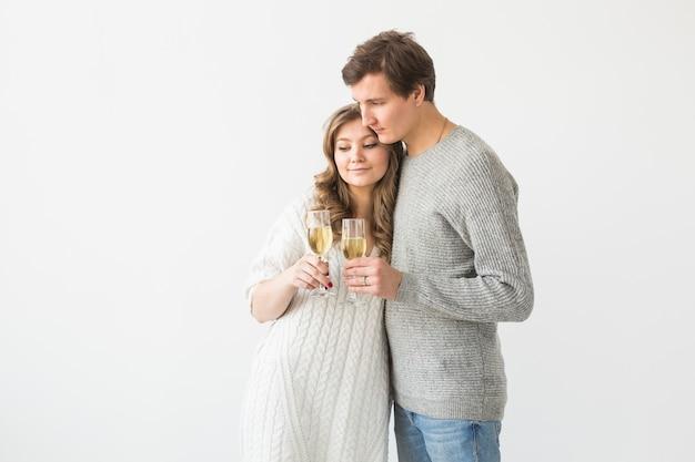 Casal apaixonado de ano novo segurando estrelinhas e taças de champanhe na parede branca com espaço de cópia