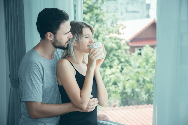 Casal apaixonado, de mãos dadas com café na manhã.