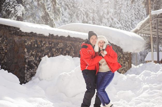 Casal apaixonado, de mãos dadas e brincando com a neve ao ar livre no inverno.