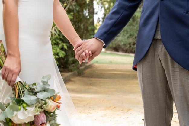 Casal apaixonado, de mãos dadas, ela com buquê em uma mão