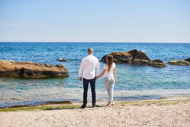 Casal apaixonado de mãos dadas em uma praia tropical com água azul-turquesa e pedras no fundo