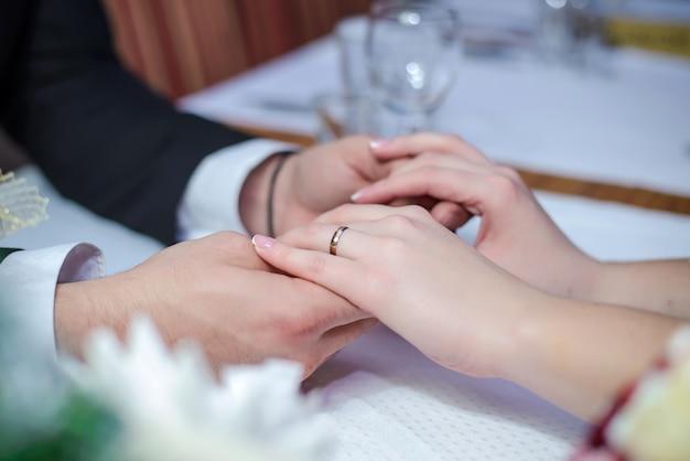 Casal apaixonado, de mãos dadas na mesa