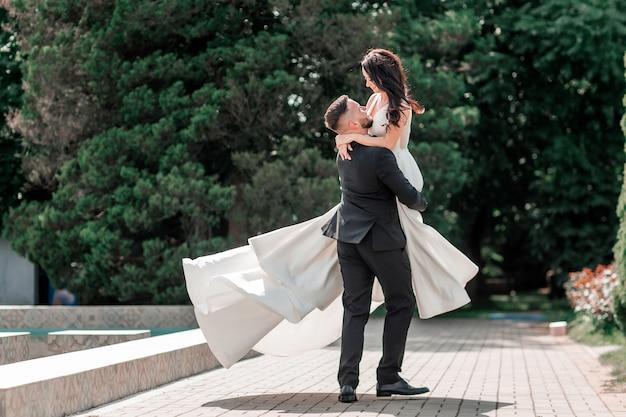 Casal apaixonado de noivos em pé no parque da cidade
