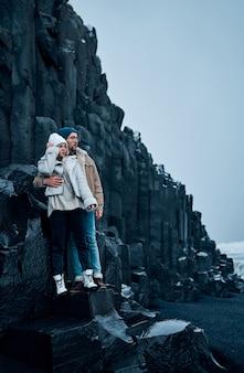 Casal apaixonado de turistas está abraçando as pedras das montanhas de basalto vulcânico negro.