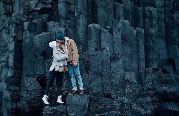 Casal apaixonado de turistas está de mãos dadas e se beijando nas pedras das montanhas de basalto vulcânico negro.