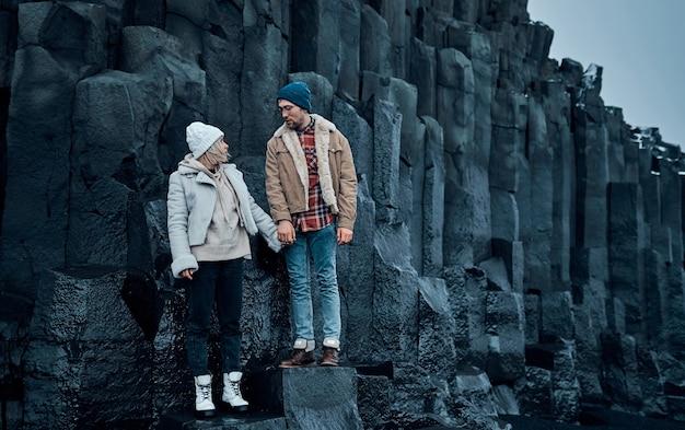 Casal apaixonado de turistas está de mãos dadas sobre as pedras das montanhas de basalto vulcânico negro.