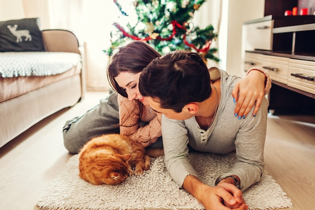 Casal apaixonado, deitado pela árvore de natal e brincando com o gato em casa. homem mulher, relaxante