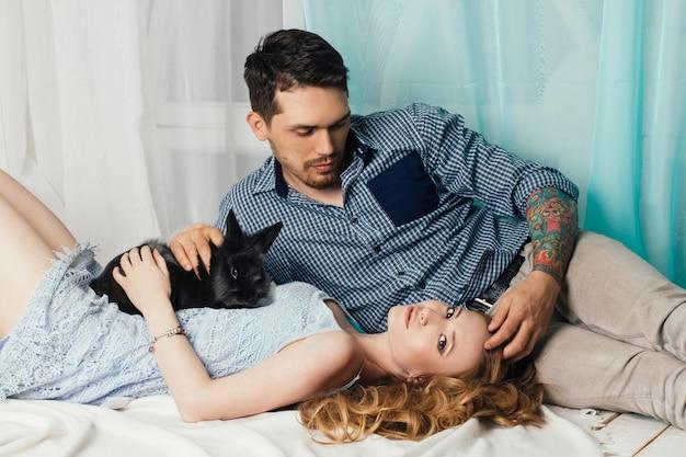Casal apaixonado, deitado perto da janela com as mãos de coelho
