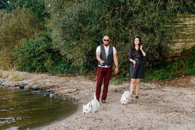 Casal apaixonado, descansando na praia com cães brancos