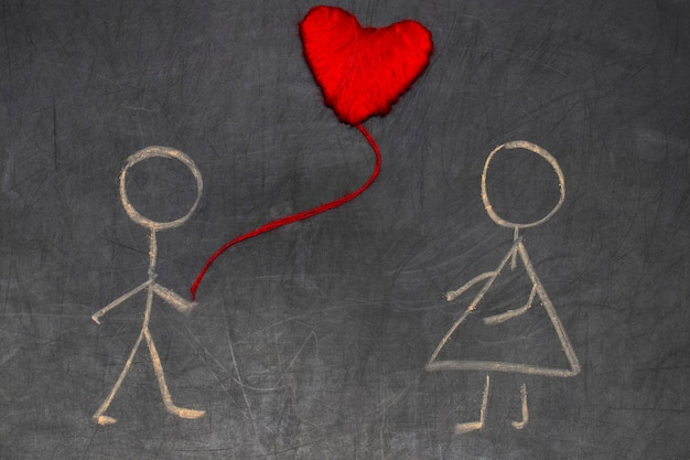 Casal apaixonado desenhando com giz no quadro-negro e o símbolo do coração vermelho para o dia dos namorados