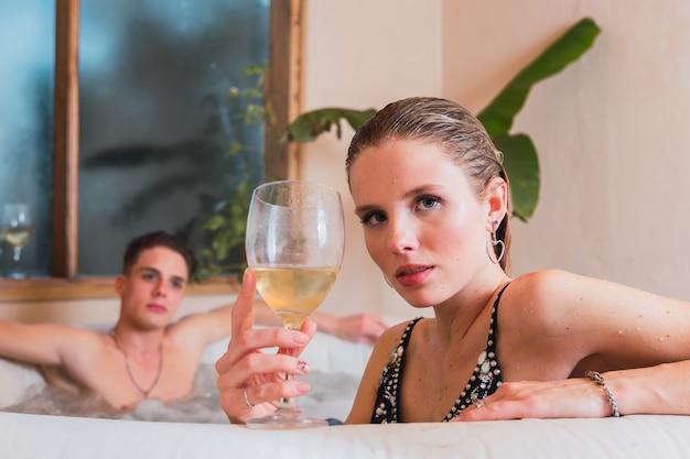 Casal apaixonado desfrutando do ambiente romântico de uma banheira jacuzzi, bebendo vinho e relaxando.