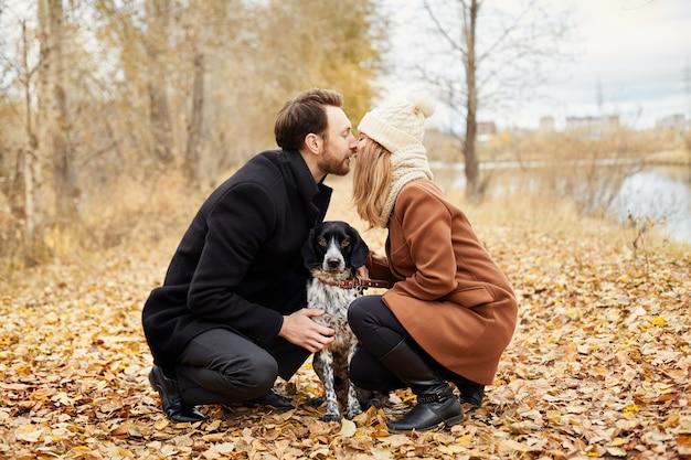 Casal apaixonado dia dos namorados andando cachorro no parque