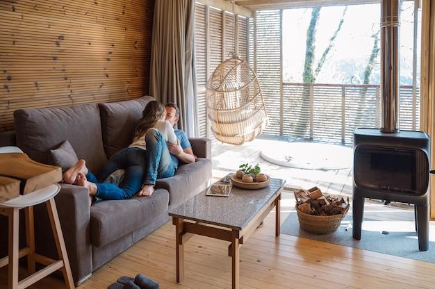 Casal apaixonado e alegre em roupas casuais se abraçando e beijando enquanto descansam juntos no sofá na elegante sala de estar com interior de madeira