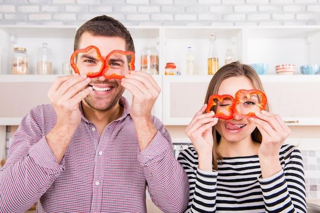 Casal apaixonado e cômico segurando fatias de pimenta perto dos olhos e mostrando a língua