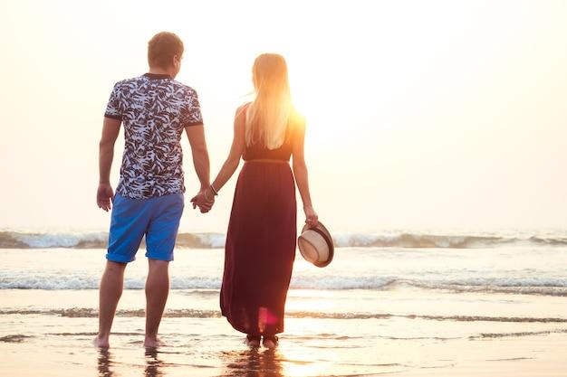 Casal apaixonado e feliz caminhando na praia. lua de mel feliz de férias românticas.