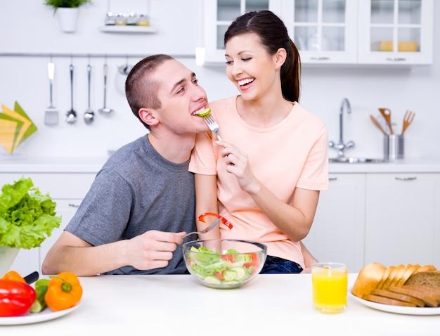 Casal apaixonado e feliz comendo salada na cozinha - dentro de casa