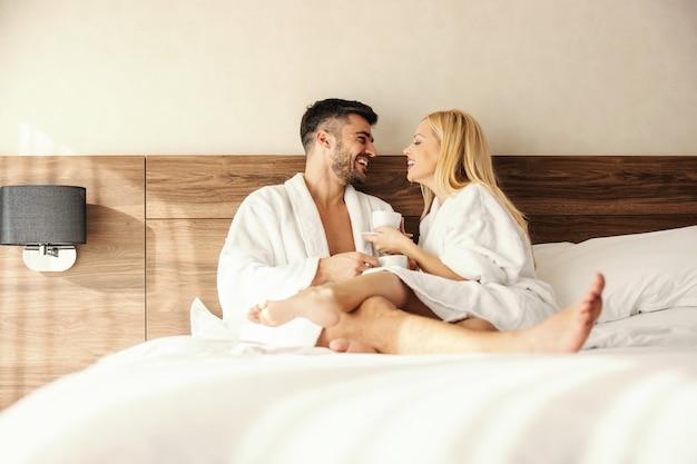 Casal apaixonado e feliz de meia-idade em um roupão de hotel conversando e rindo