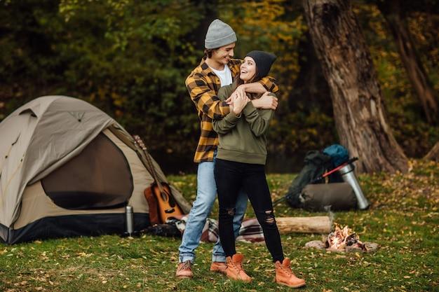 Casal apaixonado e feliz de turista em roupas casuais na floresta perto da barraca