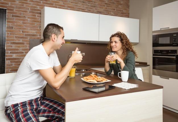 Casal apaixonado e feliz falando no café da manhã em casa