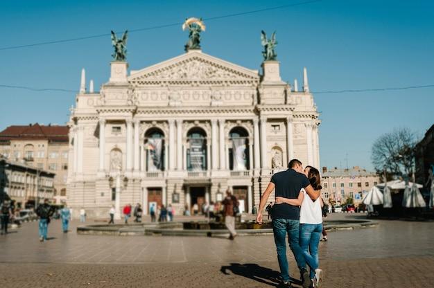 Casal apaixonado e feliz, menino beija a menina. um homem e uma mulher caminhando pelas ruas da cidade.