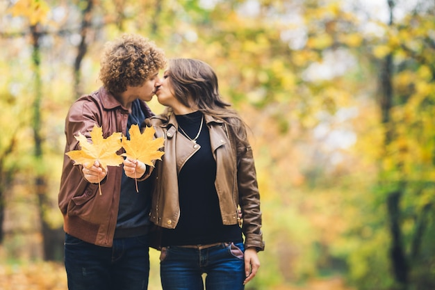 Casal apaixonado e feliz no outono no parque, segurando as folhas de bordo de outono nas mãos. garoto e garota se beijando