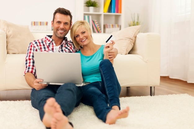 Casal apaixonado e feliz sentado no chão, usando o laptop e mostrando o cartão de crédito