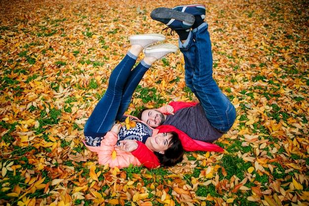Casal apaixonado é relaxante nas folhas de outono no parque