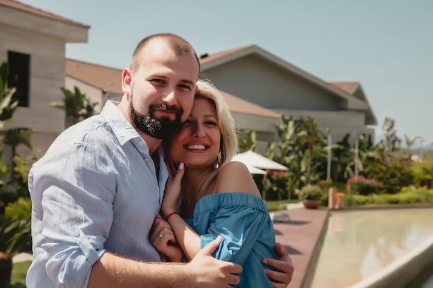 Casal apaixonado em lua de mel em hotel de luxo caminhando por jardins com palmeiras e piscina