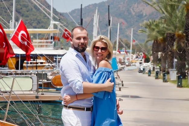 Casal apaixonado em lua de mel em um aterro com iates luxuosos