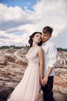 Casal apaixonado em montanhas fabulosas abraçando a paisagem de marte. os amantes caminham nas montanhas no verão, a garota com um vestido longo e leve de verão com um buquê de flores e uma coroa de flores na cabeça