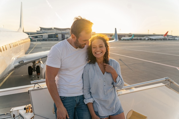 Casal apaixonado em pé na escada do avião antes do voo