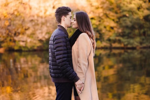 Casal apaixonado em pé no parque outono com folhas caídas amarelas. homem e mulher, aproveitando um dia juntos. garoto beijando uma garota nos lábios