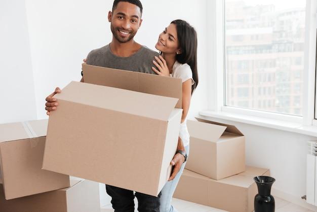 Casal apaixonado em pé perto de caixas desempacotadas. mulher abraçando o homem e olhe para ele. homem segurando a caixa nas mãos enquanto olha para frente.