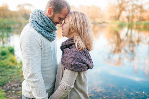 Casal apaixonado em retrato romântico de roupas de malha com lago refletido