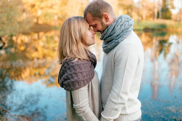 Casal apaixonado em retrato romântico de roupas de malha na frente do lago.