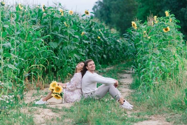 Casal apaixonado em roupas brancas posando em um campo de girassóis