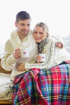 Casal apaixonado em roupas de inverno com copos de café contra a janela
