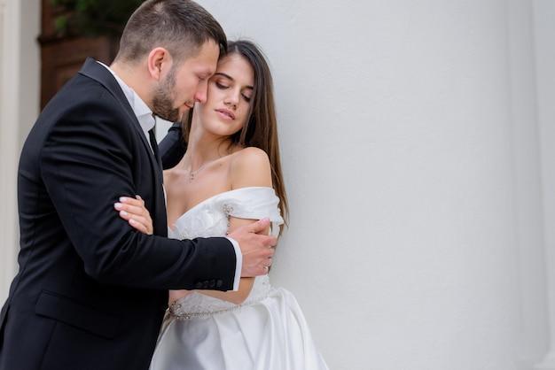 Casal apaixonado em trajes de casamento está de pé perto da parede branca, conceito de casamento