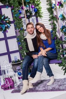 Casal apaixonado em um terraço branco senta-se no balanço