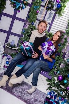 Casal apaixonado em um terraço senta-se no balanço ao lado de uma decoração de natal