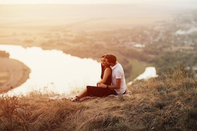 Casal apaixonado em uma manta na montanha em um piquenique à beira do rio.