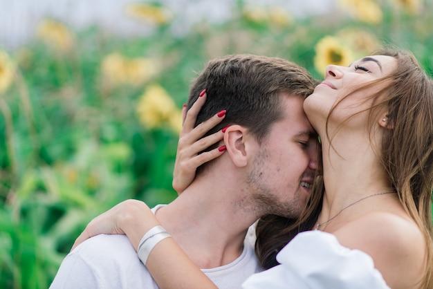 Casal apaixonado em vestidos brancos se beijando, sorrindo, rindo em um campo de girassóis