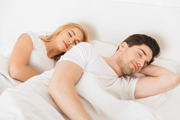 Casal apaixonado encontra-se na cama dormindo dentro de casa em casa.
