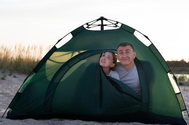 Casal apaixonado espiando de uma grande barraca verde em um acampamento