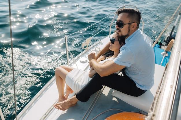 Casal apaixonado está sentado no convés do iate, abraçando-se. o casal olha para o horizonte.