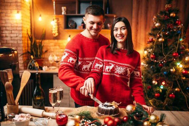 Casal apaixonado experimenta bolo de natal, comida festiva